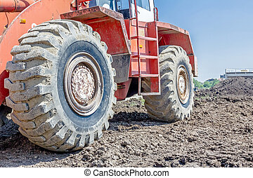 Side low angle view on undercarriage of bulldozer with big wheels, tracked