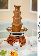 chocolate fountain stands at the wedding banquet table.