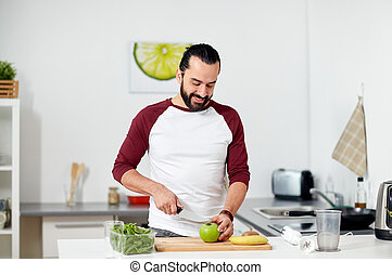 man with blender and fruit cooking at home kitchen