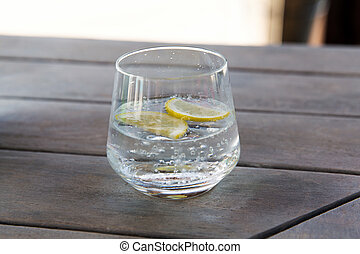 glass with cold water or cocktail on bar table - drinks and...