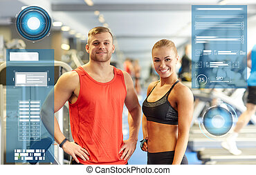 smiling man and woman in gym - sport, fitness and people...