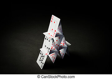 house of playing cards over black background - casino,...