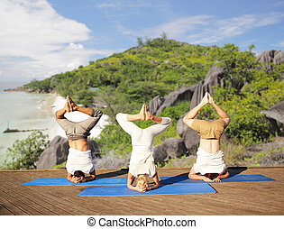 people making yoga headstand over tropical beach - fitness,...