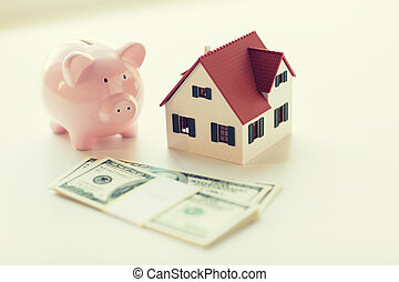 close up of house model, piggy bank and money - mortgage,...