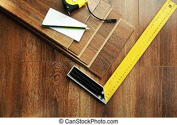 Laminate floor planks and tools on wooden background. Top view.