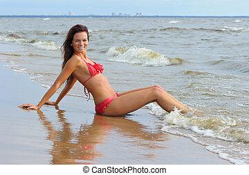Woman in bikini sitting at the coast of sea