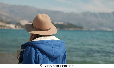 Young woman slowly walking along ocean shore. Brown-haired...