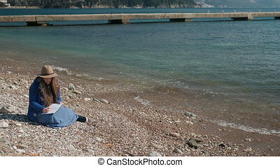 Young woman writing while sitting on beach. Brown-haired...