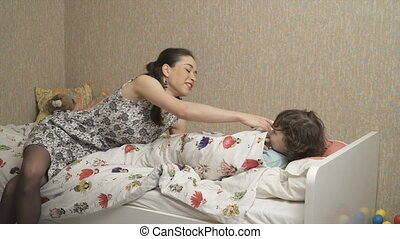 Young mother is trying to put down the daughter to the bed,...
