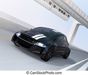 Black electric sports car driving on the highway with...