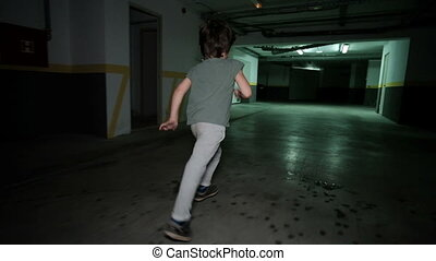 Little boy runing in underground garage, Child around...