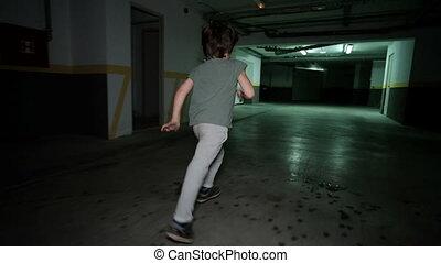 Little boy runing in underground garage, Child around...