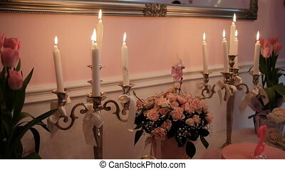 Burning candles, bouquets of flowers on table in banquet hall.