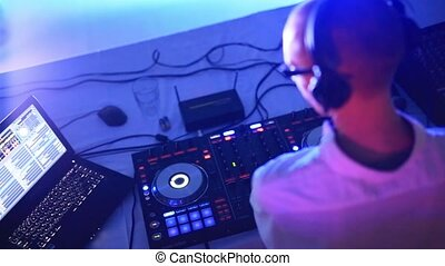 DJ plays music in the club. Musical equipment of the DJ. A...