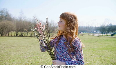 Cute ginger girl holding a spring bunch