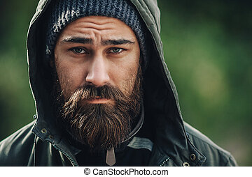 Outdor porttrait of a handsome brutal bearded man with dark...