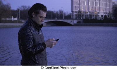Young man with a cell phone outdoors