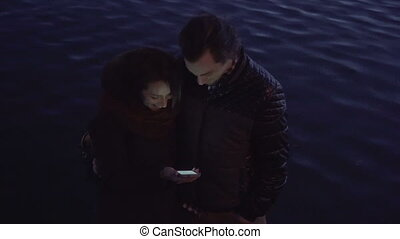Young couple with a smartphone outdoors