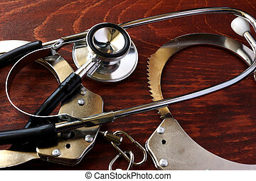 Medical negligence concept. Stethoscope and handcuffs.