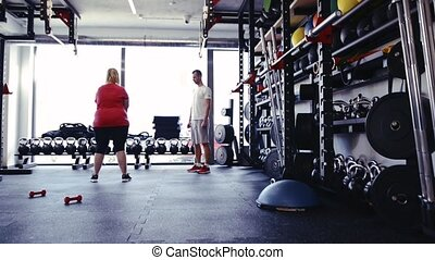 Overweight woman in gym working out with kettlebell. -...