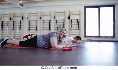 Overweight woman with her personal trainer in modern gym. -...