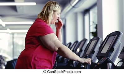 Overweight woman walking on treadmill in modern gym. -...