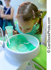 At the dentist dental patient girl spits water after...