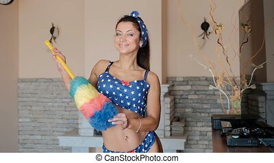 Smiling woman preparing to clean apartment swinging pom pom...