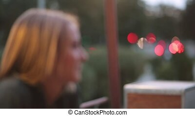 Attractive smiling young woman sitting in the city cafe. Close-up, blurred lights, urban street, side view