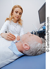 Elderly patient having ultrasonic scanning of thyroid in the clinic
