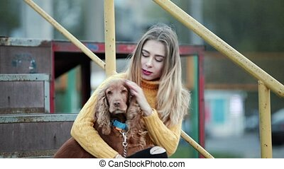Blonde woman and dog cocker spaniel strokes the dog cares...