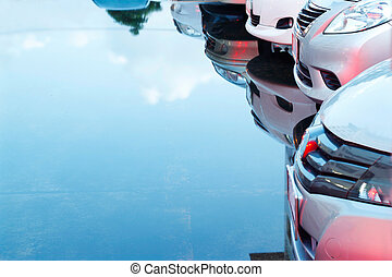 cars in parking lot and reflection in water