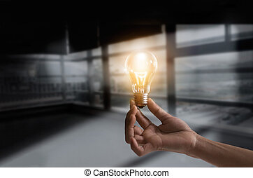 Businessman holding illuminated light bulb concept for idea, innovation and creativity inspiration concept ideas