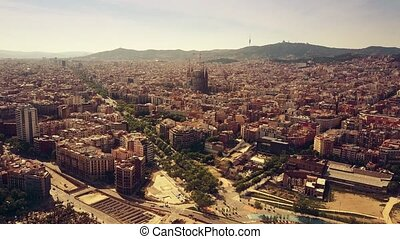 Barcelona cityscape and distant mountains on a sunny day,...
