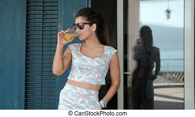 A woman in sunglasses drinks fresh orange juice from a...
