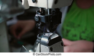 Close-up of sewing machine. Woman change s the thread and...