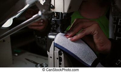 Close-up of woman s hand making stitch on the sewing...