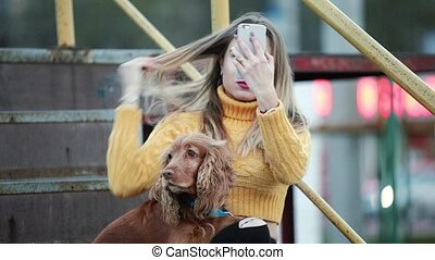 Blonde and dog-cocker spaniel Adjusts her hair looking at...