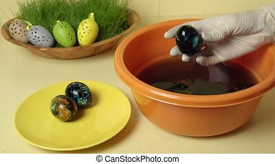 hand take painted colourful Easter eggs from water in pan....