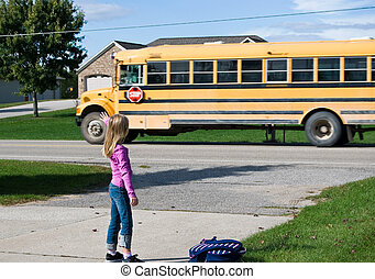 Waving Goodbye - Young girl waving goodbye to school bus.
