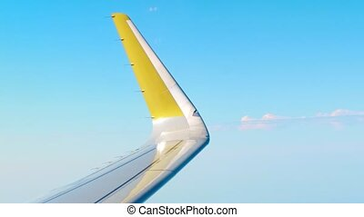 Yellow airliner wing edge against blue sky. Air travel...