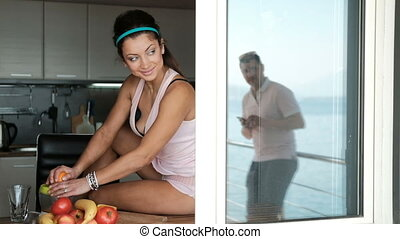 Young woman squeezes orange juice sitting by window in...