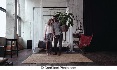 Multiethnic couple gather in travel. Woman holds suitcase, man holds plant. Boy and girl kisses and goes away.