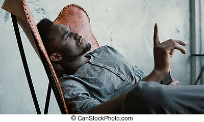 Portrait of young African man in chair. Male is seriously thinking, holding Smartphone. Guy typing message, smiling.