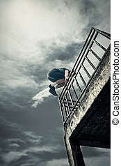 young man doing parkour jump in the city - young man doing...
