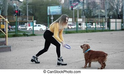 Blonde woman and dog cocker spaniel. She teases, plays,...