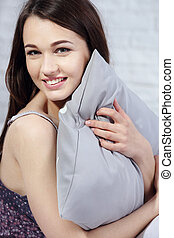 Sensual smiling young woman sitting on bed and hugging grey pillow