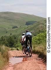 Mountain biking cyclists on path - Two bikers, cyclists, on...