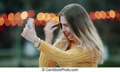Blonde woman on orange background. She fixes her hair, looking at the reflection in her smartphone.