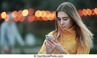Blonde types message enters text into search on the Internet in smartphone Against of yellow lights
